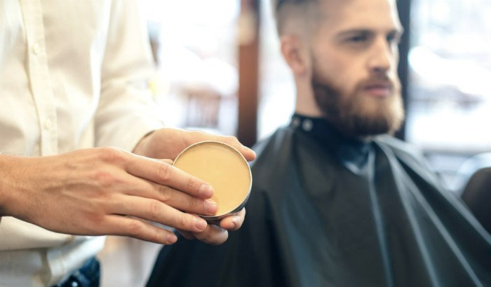 coiffeur utilisant de la cire à barbe sur le client
