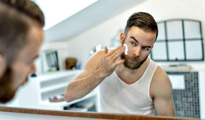homme utilisant une crème de croissance de barbe sur son visage