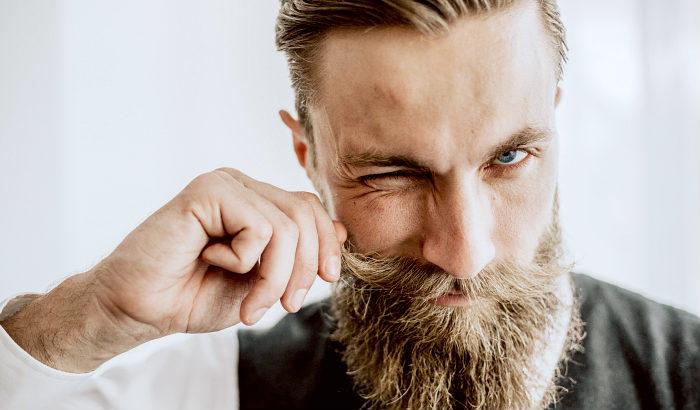 homme utilisant ses doigts pour appliquer la cire à moustache