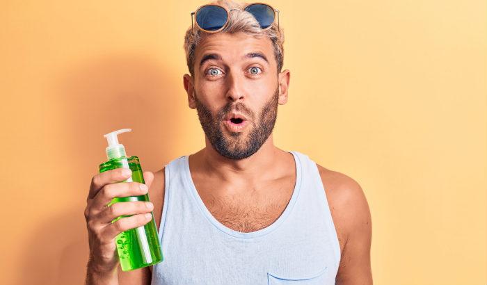 homme barbu avec une bouteille d'aloe vera