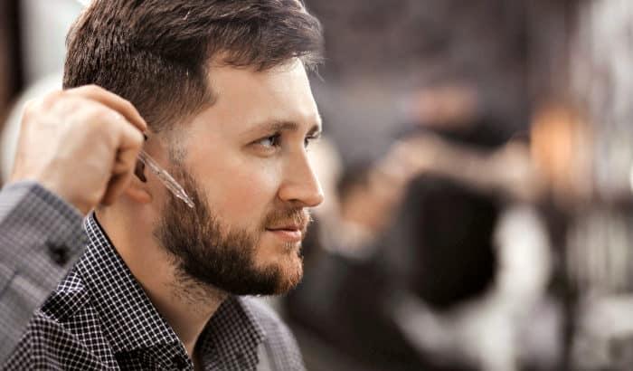 homme, appliquer de lhuile de barbe sur les joues